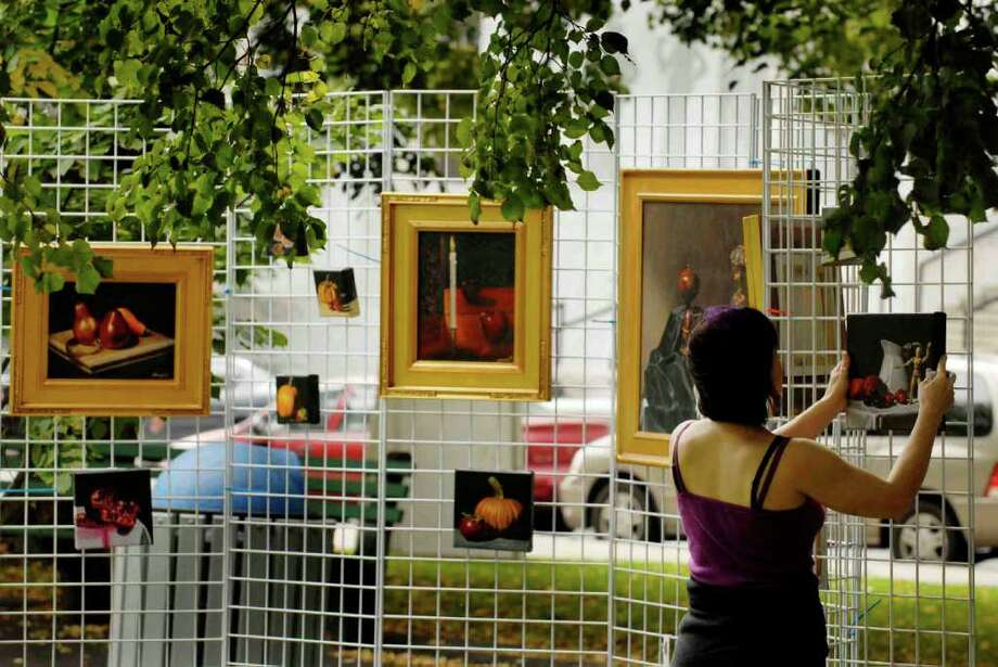 Artist Nina Stanley adjust her painting on display during an art show in the west park of the Capitol in Albany, New York 9/23/2009. (Michael P. Farrell / Times Union ) Photo: MICHAEL P. FARRELL / 00005632A