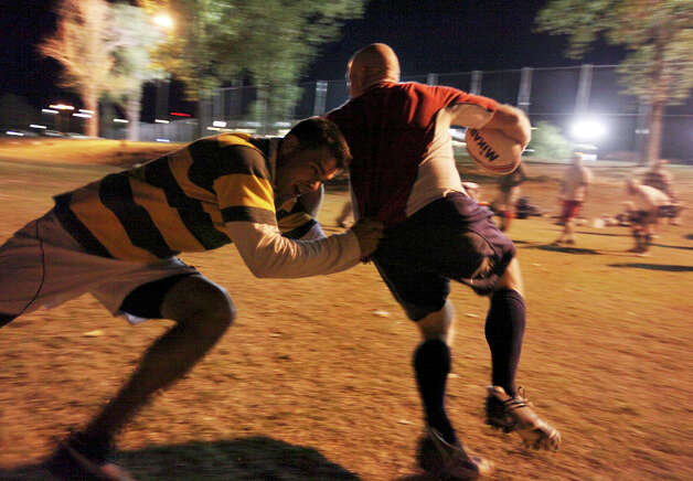 Rich Watts (left) and James Hubby take part in an Alamo City Rugby Football Club practice. Club members are proud of the ways they've helped the community, including teaching young people how to play the sport and delivering gifts for Elf Louise. Photo: EDWARD A. ORNELAS, SAN ANTONIO EXPRESS-NEWS / © SAN ANTONIO EXPRESS-NEWS (NFS)