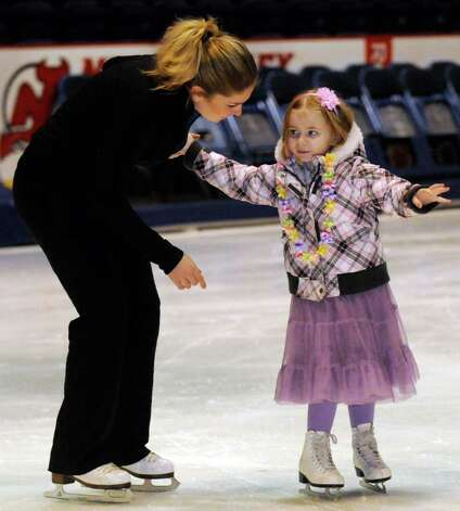 Four-year-old Lily Jones of Queensbury skate with Andrea Wolgemuth during a  Make-A-Wish  preview of Disney On Ice presents Mickey & Minnie's Magical Journey skating party at the Times Union Center in Albany NY Thursday, Dec.8, 2011.( Michael P. Farrell/Times Union) Photo: Michael P. Farrell