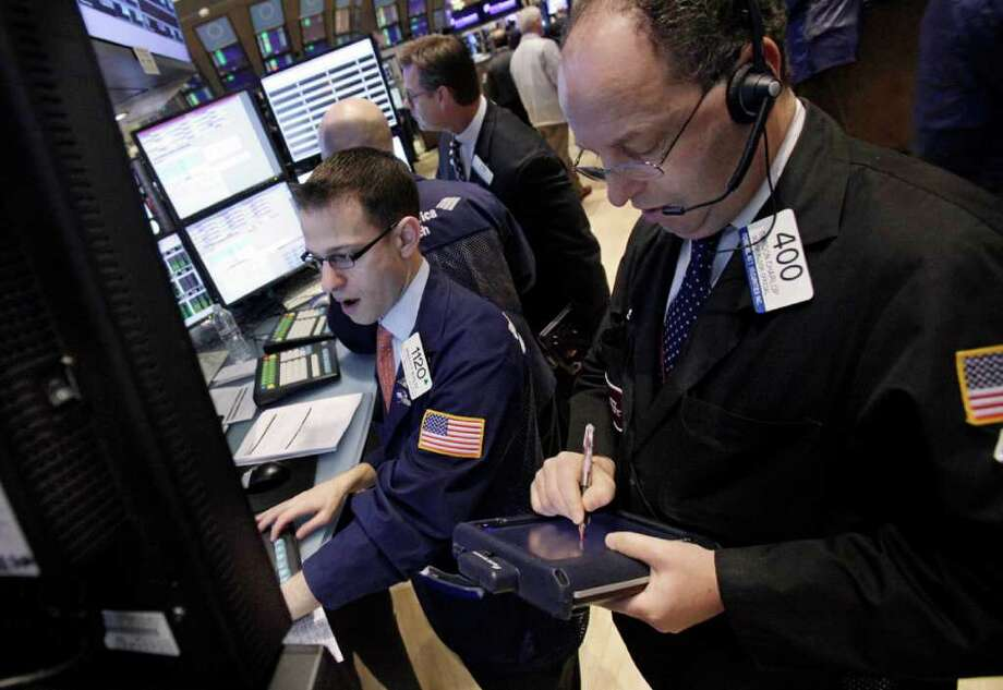 FILE - In this Dec. 5, 2011 file photo, specialist Bradley Kessler, left, and trader Gordon Charlop, right, work on the floor of the New York Stock Exchange. Markets were subdued Thursday, Dec. 8, 2011, in the run-up to a crucial summit of European Union leaders that could determine whether the euro currency survives or not. (AP Photo/Richard Drew, File) Photo: Richard Drew