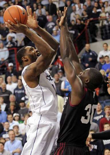 Connecticut's Alex Oriakhi takes a shot over Harvard's Kyle Casey during the first half of an NCAA c