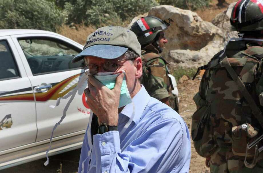 """FILE - In this June 20, 2011 photo taken during a government-organized tour for foreign diplomats and the media, US ambassador in Syria Robert Ford, covers his nose during his visit with other foreign diplomats to a mass grave, in Jisr el-Shughour, north of Syria.   State Department spokesman Mark Toner said Monday, Oct. 24, 2011, that Ambassador Robert Ford returned to Washington this weekend after """"credible threats against his personal safety.""""    (AP Photo/Bassem Tellawi, File) Photo: Bassem Tellawi / AP2011"""