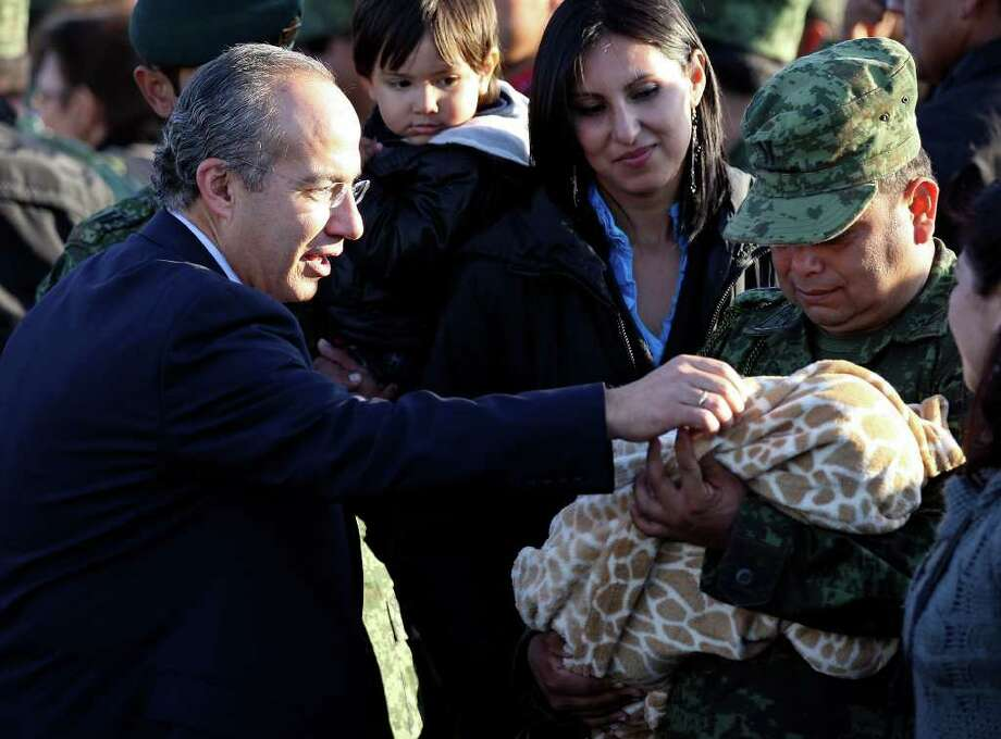 Mexican President Felipe Calderón (left) looks at a baby during a dedication ceremony for the new army base on Thursday, Dec. 8, 2011 in Ciudad Mier, Tamaulipas, Mexico. Photo: EDWARD A. ORNELAS, SAN ANTONIO EXPRESS-NEWS / © SAN ANTONIO EXPRESS-NEWS (NFS)