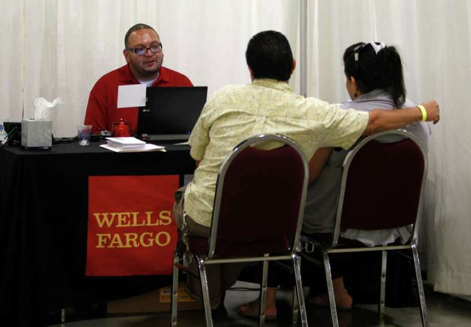 Wells Fargo employee Fermin Mercado of Milwaukee, Wis., left, talks with a couple about a loan modification during a home preservation workshop hosted by Wells Fargo, Wednesday, Dec. 7, 2011 in Fort Lauderdale, Fla. (AP Photo/ Lynne Sladky) Photo: Lynne Sladky, Associated Press / AP