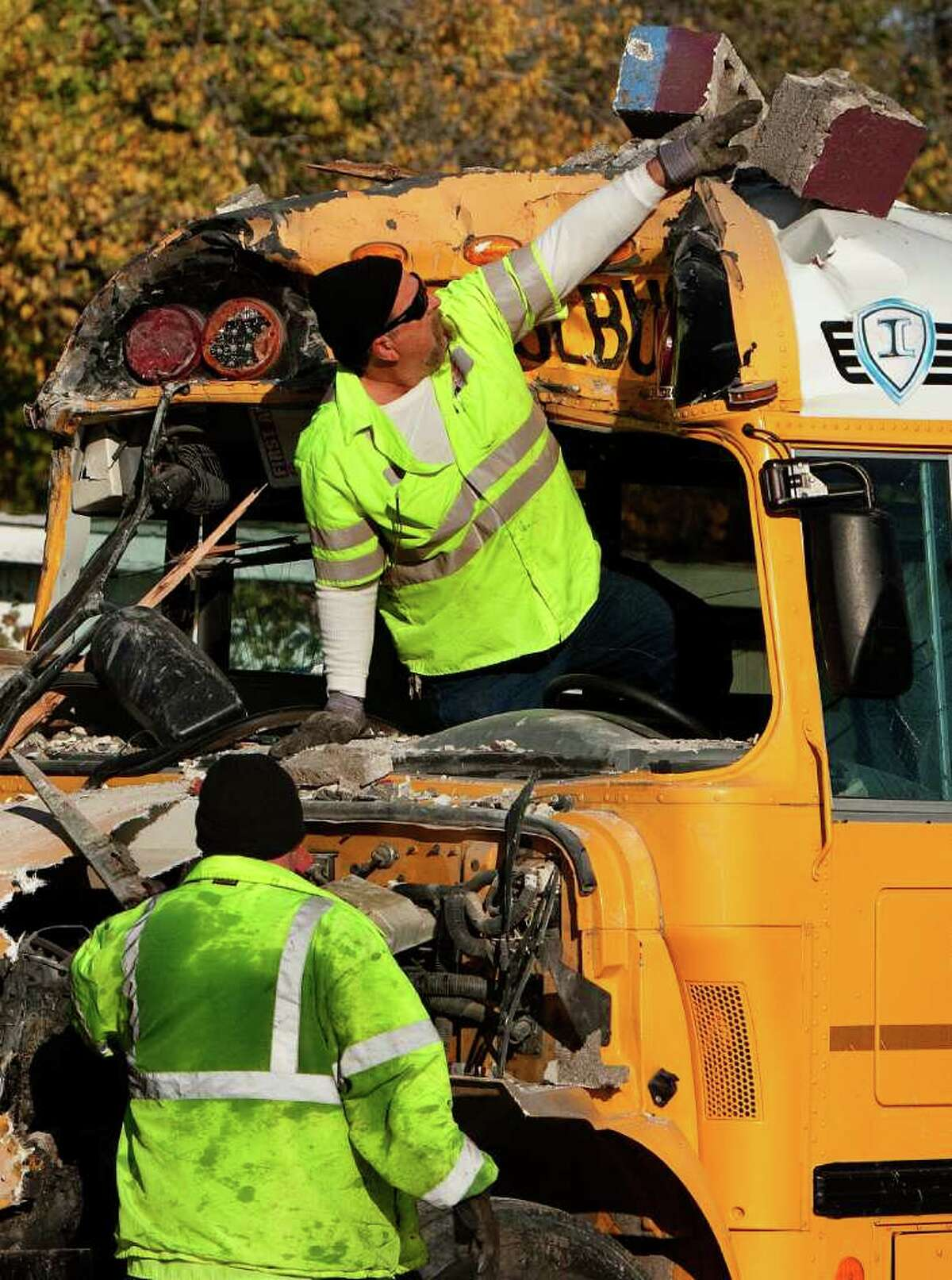Danny Cranford, left, and Greg Hembree, right, with Dan Wheeler Wrecker Service, remove debris from a school bus that crashed through a tavern wall, sending one student to the hospital.