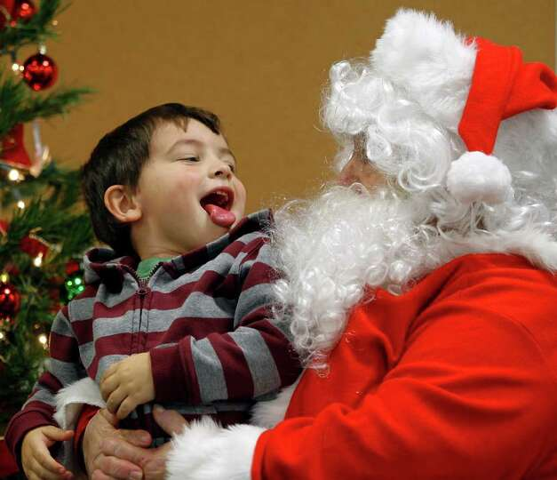 West Haslauer, 3, son of Lauren and Tim Haslauer from Slidell, shows Santa his tongue during Santa's