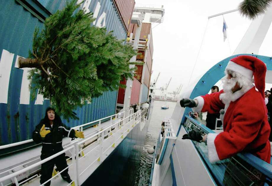 A man dressed as Santa Claus maneuvers a Christmas tree onto a ship on December 8, 2011. Every year during the Advent season, Christmas trees are distributed to the ships in the Hanseatic city. Photo: DANIEL BOCKWOLDT, Getty / DPA