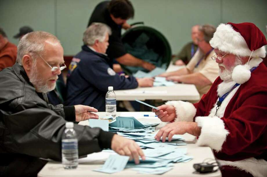 Wilson Ferguson, dressed as Santa Claus, right, and other members of the International Association of Machinists (IAM) count votes on a labor agreement proposal with Boeing Co. at the IAM Seattle Union Hall in Seattle, Washington, U.S., on Wednesday, Dec. 7, 2011. Photo: Stuart Isett, Bloomberg / 2011 Bloomberg Finance L.P.