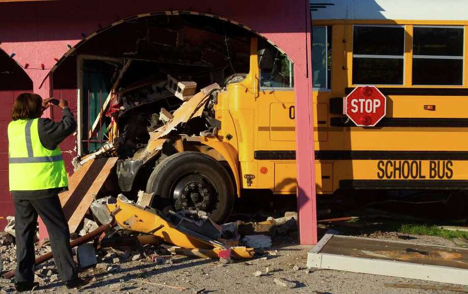 Betty Johnson with First Student, Inc., takes a photo of a school bus that was involved in an accident Thursday, Dec. 8, 2011, in Houston. The accident occurred about 7:15 a.m. at 7400 E. Hardy Road near Crosstimbers. Photo: Cody Duty, Houston Chronicle / © 2011 Houston Chronicle