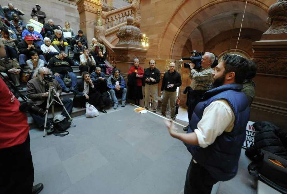 "SUNYA student and Occupy Albany member Colin Donnaruma, right leads a discussion of ""The Real Rent Reform"" campaign on the steps of the Million Dollar staircase in the State Capitol in Albany, N.Y. Dec. 8, 2011.    (Skip Dickstein/Times Union) Photo: Skip Dickstein"