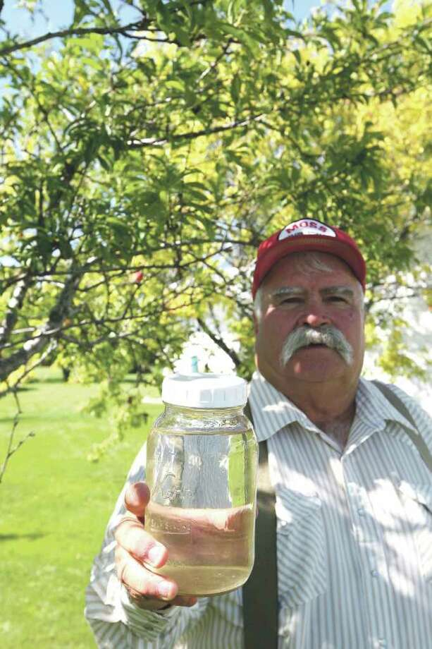 Pavillion, Wyo., resident Louis Meeks holds a jar of water from a well he says was tainted by hydraulic fracturing. Photo: Kerry Huller / Copyright 2011 CASPER STAR-TRIBUNE