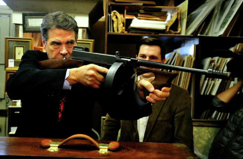 Texas Gov. Rick Perry, looks down the barrel of a vintage 1928 Thompson submachine gun at the Rhett Gallery in Beaufort, S.C.