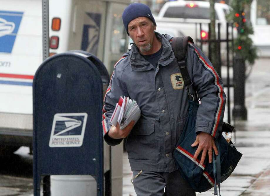 A mail carrier delivers mail in Montpelier, Vt. The U.S. Postal Service is facing yet another round of cost-cutting.  Maybe more automation is among the answers. Photo: Associated Press, Toby Talbot