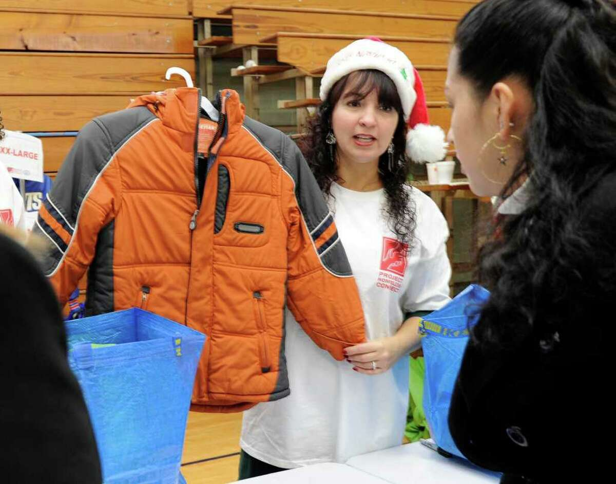 Marisol Lens, of Union savings Bank, offers a winter jacket to Norma Balberde, at Project Homeless Connect held at the Western Connecticut State University's downtown campus Friday. Photo taken Friday, Dec. 9, 2011.
