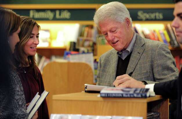 "Former President Bill Clinton autographs a copy of his book, ""Back to Work: Why We Need Smart Government for a Strong Economy,"" for Yvonne Nichols, left, of Darien, and Andrea O'Connor, of Rye, NY, Friday, Dec. 9, 2011 at Barrett Bookstore in Darien, Conn. Photo: Autumn Driscoll / Connecticut Post"