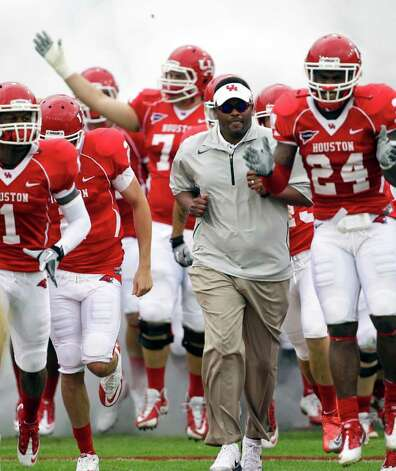 FILE - In this Nov. 19, 2011, file photo, Houston coach Kevin Sumlin, center, leads his team onto the field for an NCAA college football game against SMU in Houston. Houston celebrates its upcoming move from Conference USA to the Big East amid continued speculation that coach Kevin Sumlin could be leaving for another job. Photo: AP