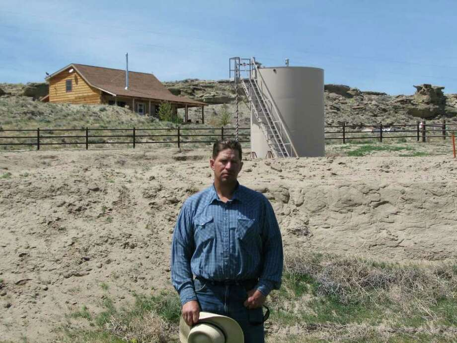 "FILE - This May 22, 2009 picture shows John Fenton, a farmer who lives near Pavillion in central Wyoming, near a tank used in natural gas extraction, in background. Fenton and some of his neighbors blame hydraulic fracturing, or ""fracking,"" a common technique used in drilling new oil and gas wells, for fouling their well water. The U.S. Environmental Protection Agency announced Thursday Dec. 8, 2011 in Wyoming, for the first time that fracking may be to blame for causing groundwater pollution. The EPA also emphasized that the findings are specific to the Pavillion area. The agency said the fracking that occurred in Pavillion differed from fracking methods used elsewhere in regions with different geological characteristics. Photo: AP"
