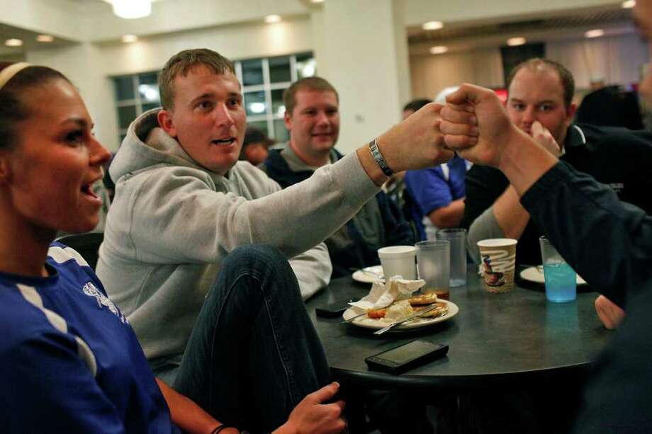 "Dakota Meyer, center, gives his half-brother, Timothy Gilliam, 19, a fist bump during the ""Midnight Breakfast,"" a tradition for the start of finals week at Lindsey Wilson College, where Meyer has an office, many mentors and will be receiving an Honorary Doctorate Degree on Saturday, on Tuesday, Dec. 6, 2011. Meyer is surrounded by his girlfriend, Sara Sells, from left, a House Manager at the college, Mike Staten, Director of Public Safety at the college and Jordan Willis, Men's Area Coordinator at the college.  Photo: LISA KRANTZ, SAN ANTONIO EXPRESS-NEWS / SAN ANTONIO EXPRESS-NEWS"