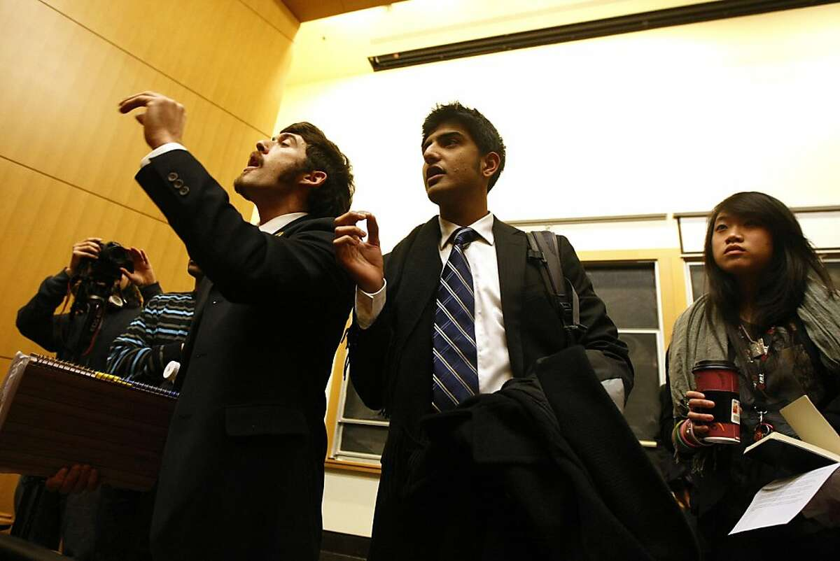 ASUC Senators Shahryar Abbasi (center, right) and Elliot Goldstein (center, left) attempt to calm protesters after UC Berkeley Chancellor Robert Birgeneau abruptly abandoned his address in the Berdahl Room of Stanley Hall in Berkeley, Calif., on Wednesday, Dec. 6, 2011. Chancellor Birgeneau was repeatedly interrupted by raucous protesters until deciding to leave the meeting. Ran on: 12-09-2011 Elliot Goldstein (left) and Shahryar Abbasi of UC Berkeleys student senate try to calm protesters Wednesday.