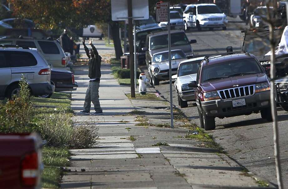 Detwone Watson, the suspect in a San Leandro Black Friday shooting, comes out of a home with his hands up after a standoff with police in Oakland, Calif., Thursday, December 8, 2011. Photo: Sarah Rice, Special To The Chronicle