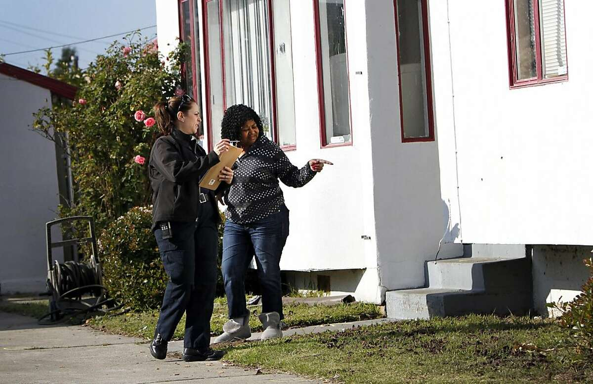 Jean Beal points out bullet holes in the side of her home to an investigator after a home invasion next door ended in gunfire in Richmond, Calif., Thursday, December 8, 2011. A Richmond man allegedly shot two robbers, one fatally, when they broke into his home.