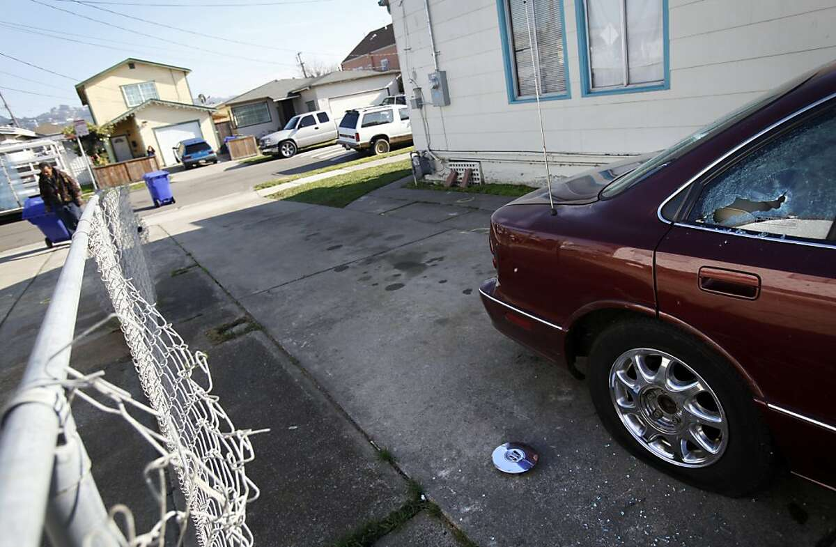 A car window is shattered by gunfire, and the driveway to this home is marked with yellow evidence chalklines after a home invasion ended in gunfire in Richmond, Calif., Thursday, December 8, 2011. A Richmond man allegedly shot two robbers, one fatally, when they broke into his home.