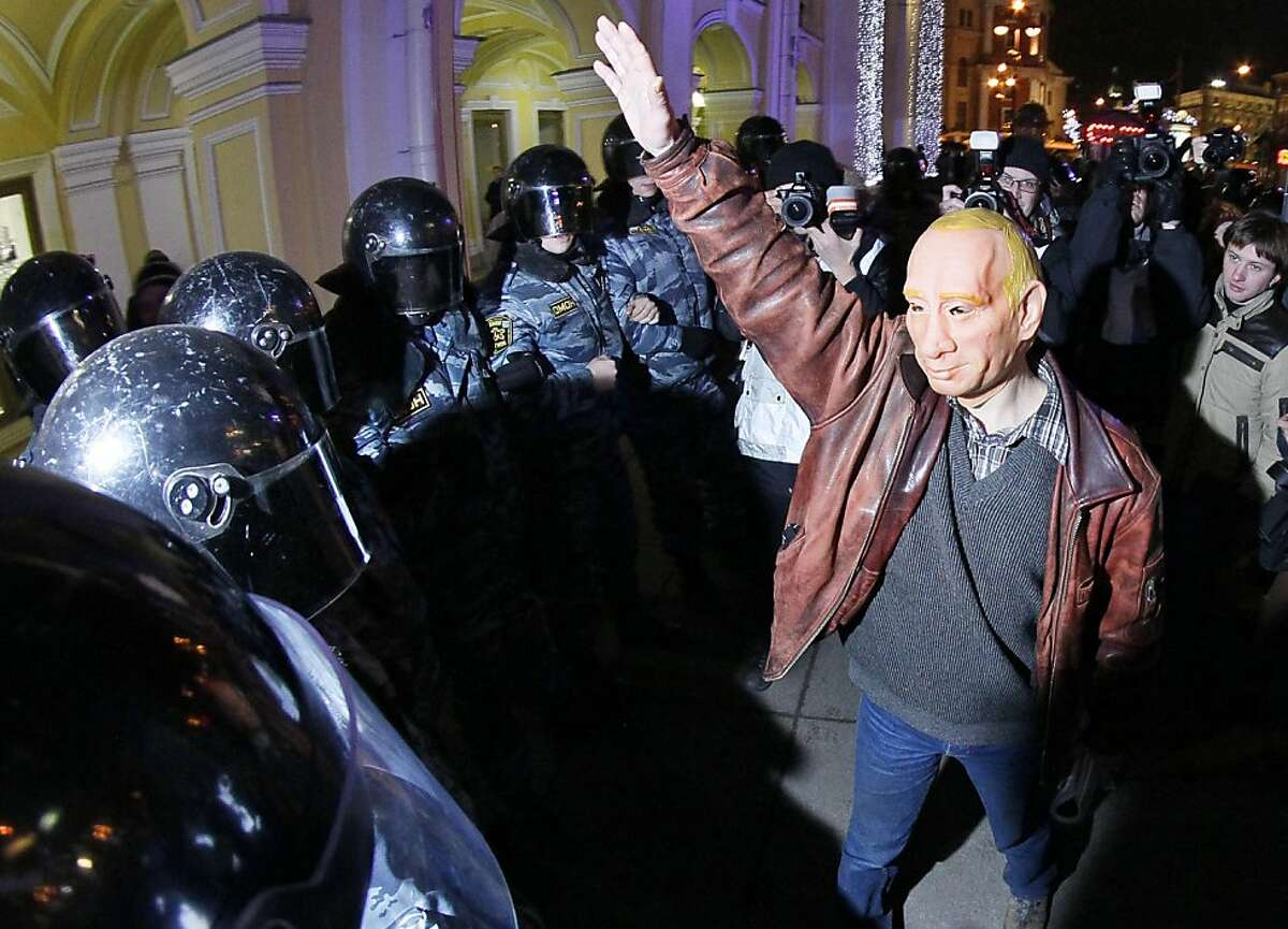 Riot police, OMON, surround a protester wearing a mock mask depicting Russian Prime Minister Vladimir Putin during a rally in downtown St.Petersburg, Russia, Thursday, Dec. 8, 2011. More than five hundreds people have protested in St.Petersburg against Prime Minister Vladimir Putin and his party, which won the largest share of a parliamentary election that observers said was rigged. (AP Photo/Dmitry Lovetsky)