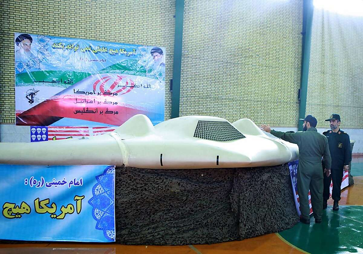 """A picture released by the official website of Iran's Revolutionary Guards on December 8, 2011 shows Iranian Revolutionary Guard, Brigadier General Amir-Ali Hajizadeh (R) looking at what Iranian officials claim is the US RQ-170 Sentinel high-altitude reconnaissance drone that crashed in Iran on December 4, 2011 displayed at an undisclosed location. Revelations about the US reconnaissance drone suggest Washington is stepping up surveillance and pressure on the Islamic republic over its nuclear program, media reports say. Slogans on banner read in Farsi """"Death to America, death to Israel, death to England."""" AFP PHOTO/HO/IRAN'S REVOLUTIONARY GUARD WEBSITE RESTRICTED TO EDITORIAL USE - MANDATORY CREDIT """" AFP PHOTO / IRAN'S REVOLUTIONARY GUARD WEBSITE"""" NO MARKETING NO ADVERTISING CAMPAIGNS - DISTRIBUTED AS A SERVICE TO CLIENTS EDS NOTE: AFP IS USING PICTURES FROM ALTERNATIVE SOURCES AS IT WAS NOT AUTHORISED TO COVER THIS EVENT, THEREFORE IT IS NOT RESPONSIBLE FOR ANY DIGITAL ALTERATIONS TO THE PICTURE'S EDITORIAL CONTENT, DATE AND LOCATION WHICH CANNOT BE INDEPENDENTLY VERIFIED == (Photo credit should read -/AFP/Getty Images)"""