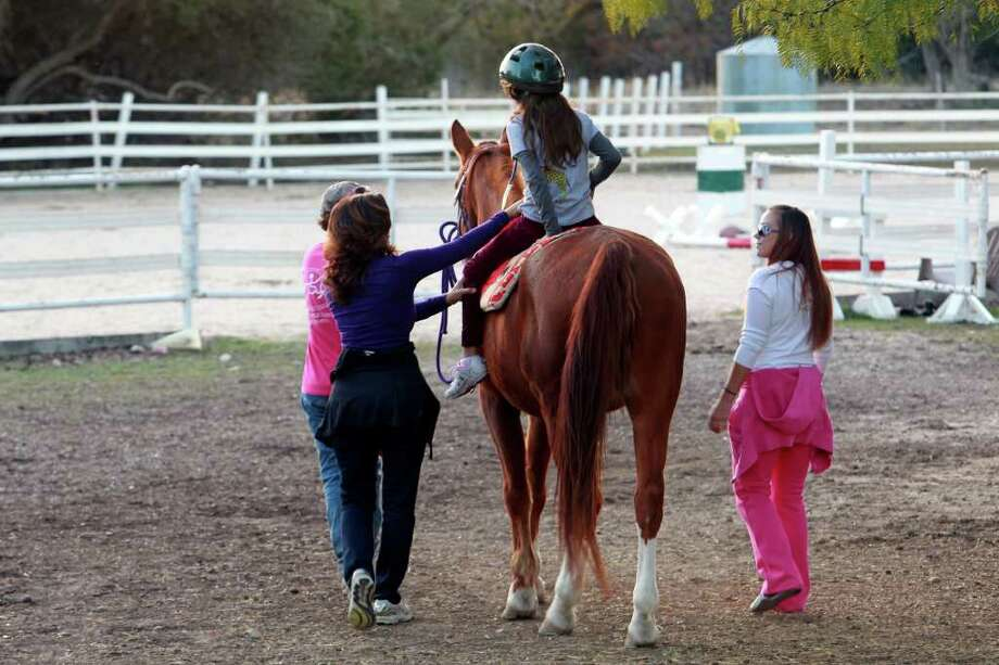 Marissa Pate rides under watchful eye of parent and trainers as the Triple H Equitherapy   Center helps children and adults with physical and learning disabilities, wounded warrors and at-risk youth by using horses as a form of therapy. Photo: TOM REEL, SAN ANTONIO EXPRESS-NEWS / © 2011 San Antonio Express-News