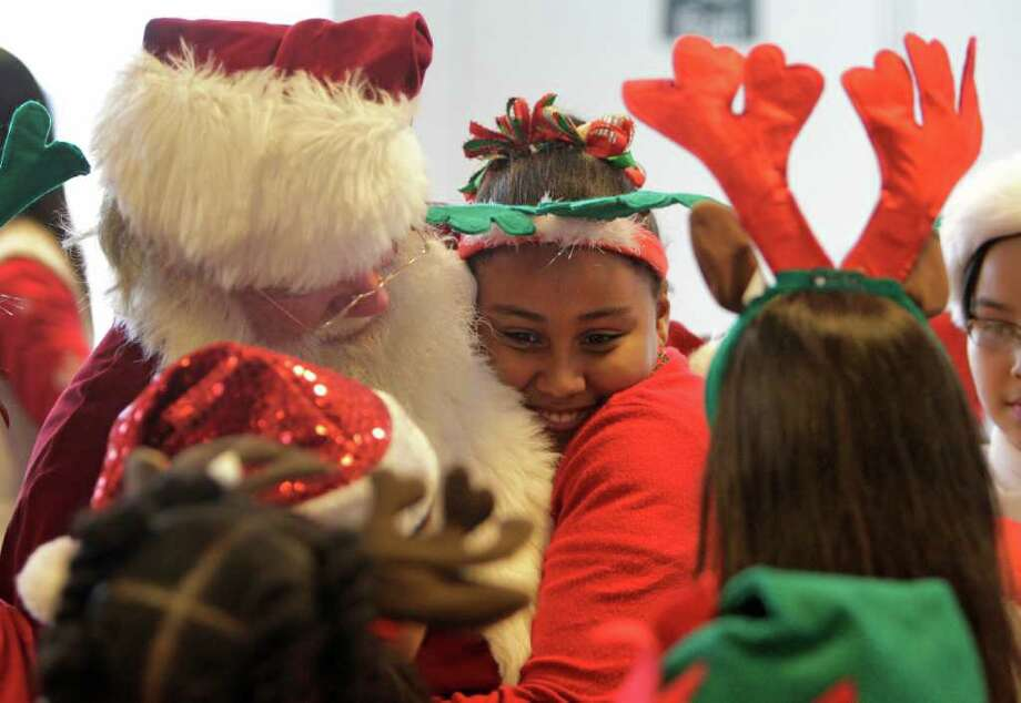 Aaliyah Dixon, 9, a 4th grader at Heritage Elementary School in Spring ISD hugs Santa after a performance by the Heritage Harmony Choir during the American Airlines Snowball Express event at Bush Intercontinental Airport. The choir sang as part of the send off for nine military families who departed to join the nearly 1,700 children and spouses of fallen U.S. military soldiers on an all-expense-paid trip to Dallas/Fort Worth for the sixth annual Snowball Express. Photo: Melissa Phillip, Houston Chronicle / © 2011 Houston Chronicle