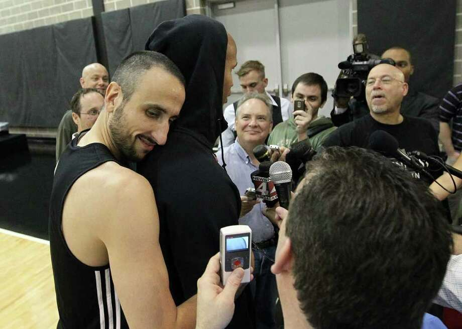 Manu Ginobili (left) offers a hug to teammate Richard Jefferson during Jefferson's interview session with media as players for the San Antonio Spurs attend their first team practice on Friday, Dec. 9, 2011.  Kin Man Hui/kmhui@express-news.net Photo: KIN MAN HUI, Express-News / SAN ANTONIO EXPRESS-NEWS