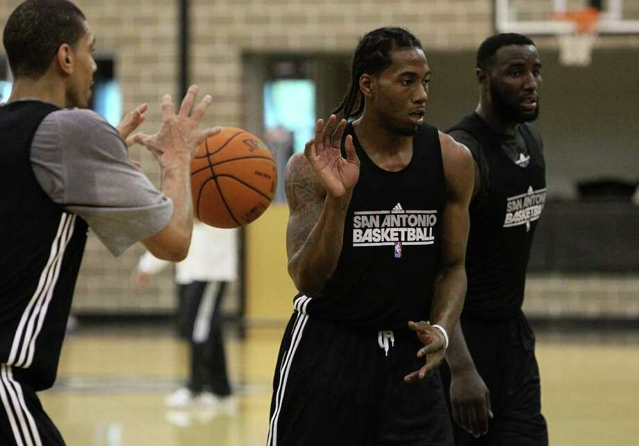 Spurs rookie Kawhi Leonard (center) tosses the ball to Danny Green (left) alongside DeJuan Blair (right) as players for the San Antonio Spurs attend their first team practice on Friday, Dec. 9, 2011.  Kin Man Hui/kmhui@express-news.net Photo: KIN MAN HUI, Express-News / SAN ANTONIO EXPRESS-NEWS