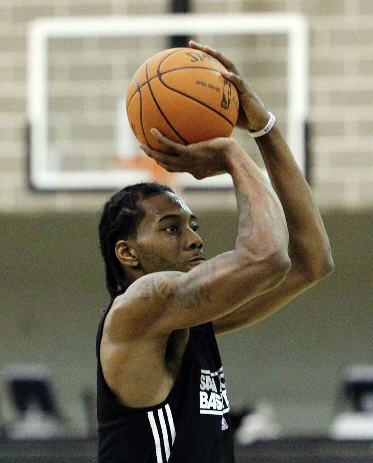 3. Leonard practices with the Spurs Photo: Spurs rookie Kawhi Leonard focuses on taking a shot as players for the San Antonio Spurs attend their first team practice on Friday, Dec. 9, 2011.