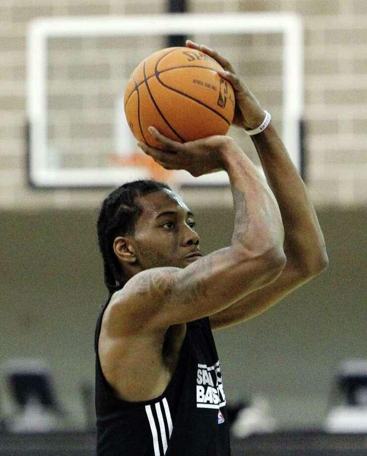 Spurs rookie Kawhi Leonard focuses on taking a shot as players for the San Antonio Spurs attend their first team practice on Friday, Dec. 9, 2011.  Kin Man Hui/kmhui@express-news.net Photo: KIN MAN HUI, Express-News / SAN ANTONIO EXPRESS-NEWS