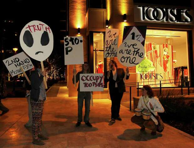 "Members of Occupy Tootsies an ""art"" demonstration to show what a protest by the richest 1 percent of America would look like, stand outside of Tootsies on the corner of Kirby and Westheimer, Dec. 9, 2011, in Houston. Photo: Karen Warren, Houston Chronicle / © 2011 Houston Chronicle"
