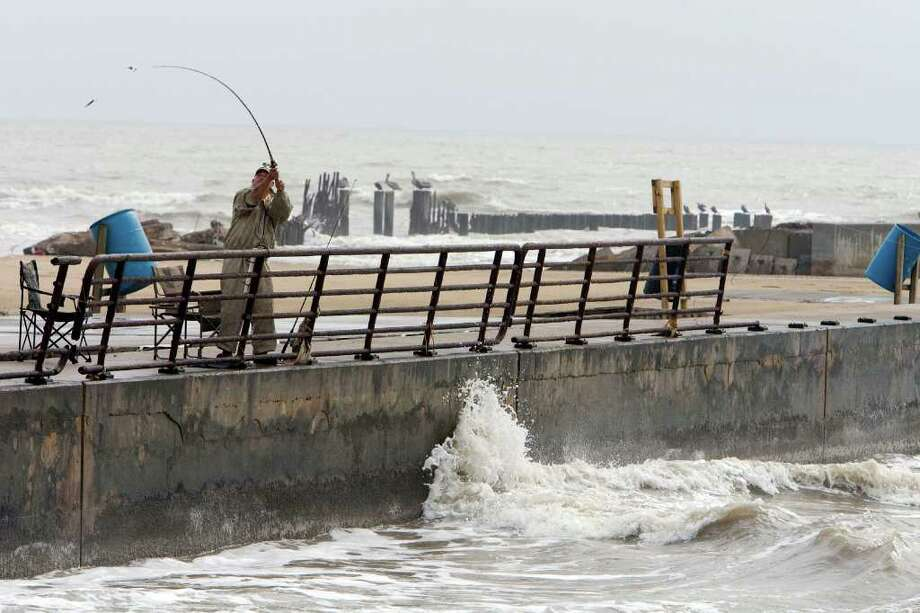 Auda Derby, of Greenville, casts into the surf at Rollover Pass on the Bolivar Peninsula last month. The pass is slated for closure by the Texas General Land Office in 2012. A lighted fishing pier has been proposed for the area. Photo: James Nielsen / Houston Chronicle