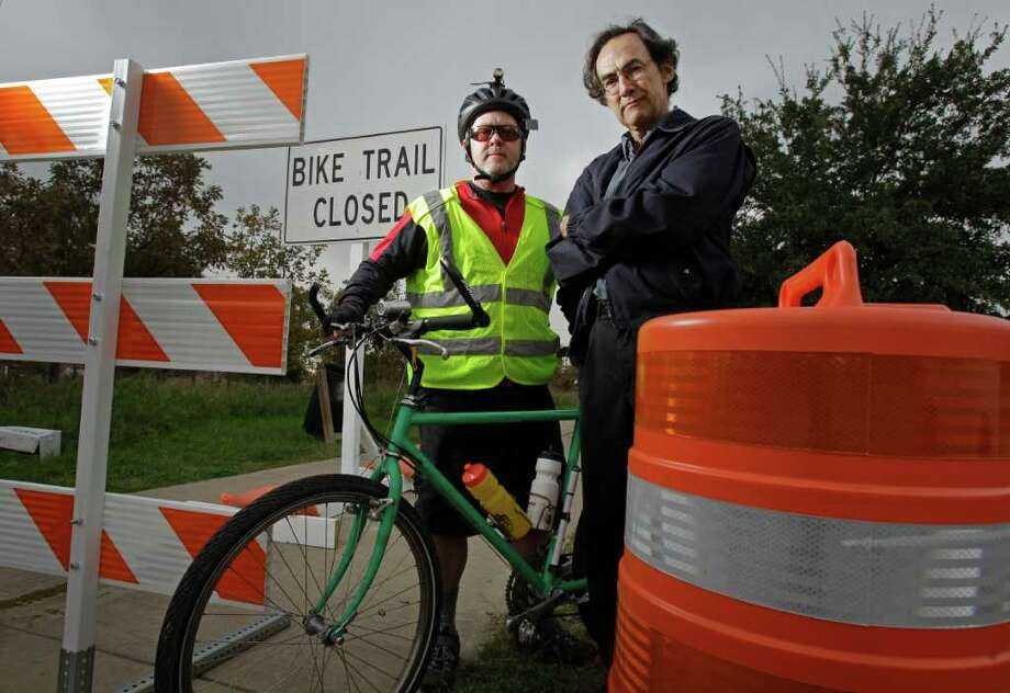 Tom Gall, left, and David Dick are up against their nemesis - the barricade that puts off-limits a mile-long stretch of the White Oak Bayou Hike and Bike Trail. Photo: Melissa Phillip / © 2011 Houston Chronicle