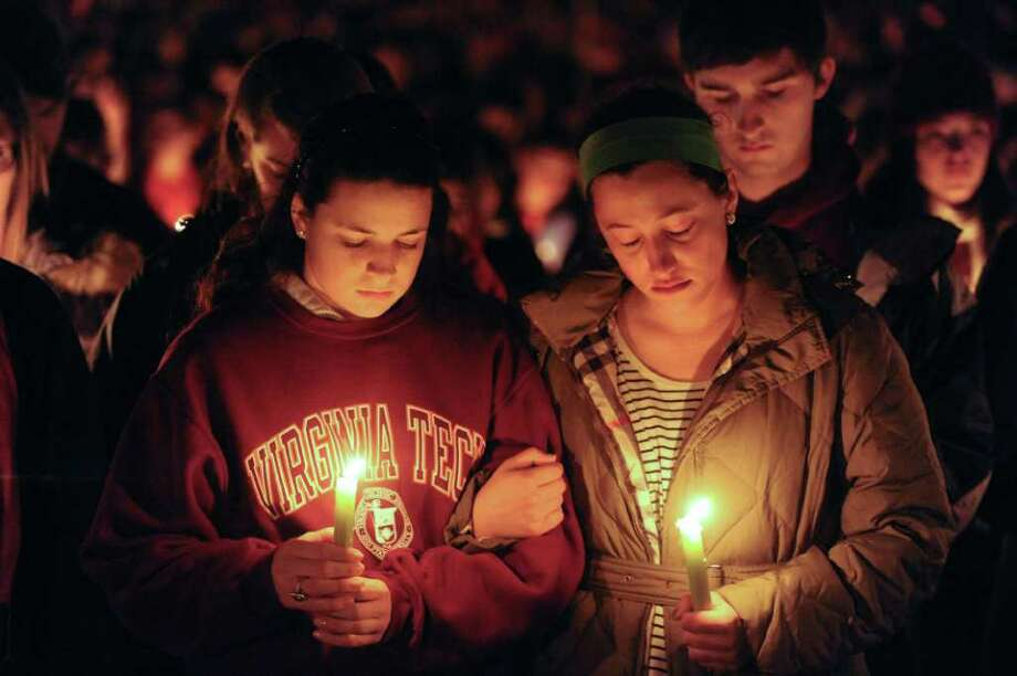 Virginia Tech students hold a candlelight vigil on the drill field on campus as a memorial to Virginia Tech police Officer Deriek Crouse, who was gunned down Thursday during a traffic stop on the campus of Virginia Tech in Blacksburg, Va., Friday, Dec. 9, 2011. Photo: Don Petersen, Associated Press / FR59093 AP