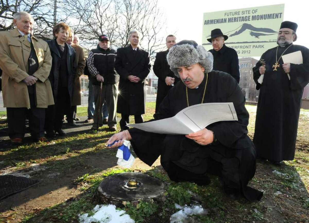 The Rev. Stepanos Doudoukjian waves a religious instrument over some incense while reading during service for the future Armenian Heritage Monument in Troy Riverfont Park on Friday, Dec. 9, 2011 in Troy, N.Y. (Lori Van Buren / Times Union)
