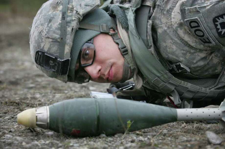 Staff Sgt. Christopher Phelps of Fort Campbell, Kentucky, closely examines an 81mm mortar round as he prepares to safely explode the device during 20th SUPCON Team Leader Training Academy hosted at Joint Base Lewis-McChord, Wash. Photo: Tony Overman, Associated Press / The Olympian