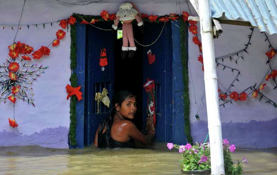 Xiomara Herrera, 13, enters her flooded home in El Porvenir, southern Colombia, Friday, Dec. 9, 2011. Torrential rains have caused devastating floods and widespread damage in the country for much of the past two years. Photo: Carlos Julio Martinez, Associated Press / AP