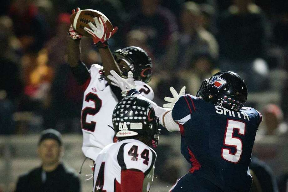 Coldspring defensive back Douglas Johnson (2) intercepts a pass intended for Wimberly running back Dennis Smith. Photo: Smiley N. Pool, Houston Chronicle / © 2011  Houston Chronicle