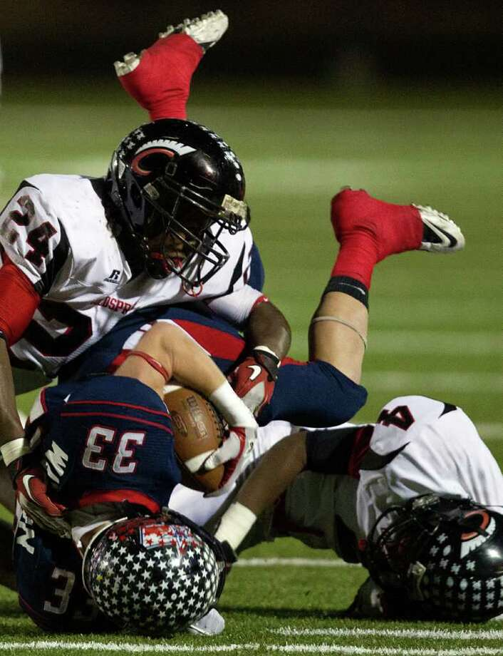 Wimberley running back Trinity Wilson (33) is brought down by Coldspring defenders Patrick Giddens (24) and Jerrell Sykes. Photo: Smiley N. Pool, Houston Chronicle / © 2011  Houston Chronicle