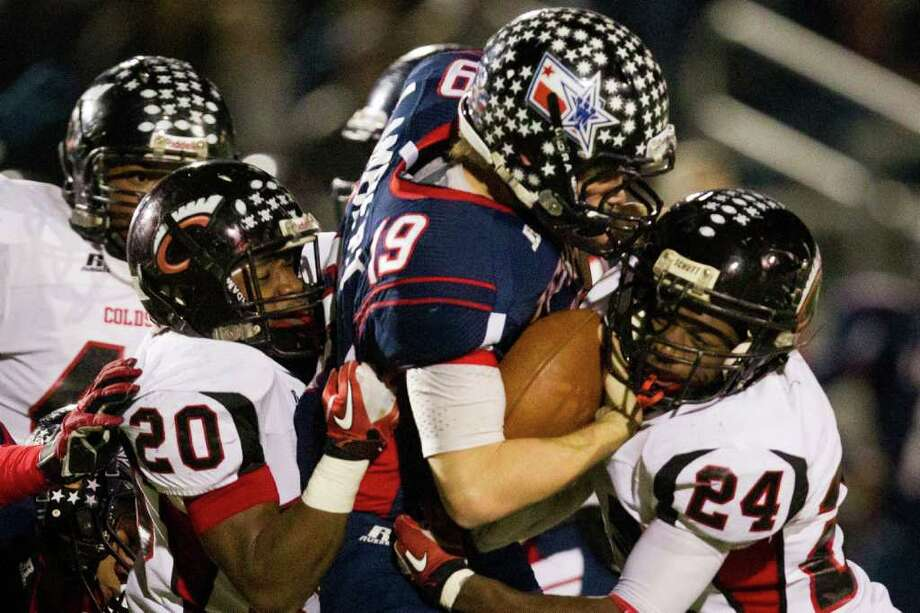 Coldspring defenders Trey Cooper (20) and Patrick Giddens (24) combine to drop Wimberley quarterback Brady Lambert. Photo: Smiley N. Pool, Houston Chronicle / © 2011  Houston Chronicle