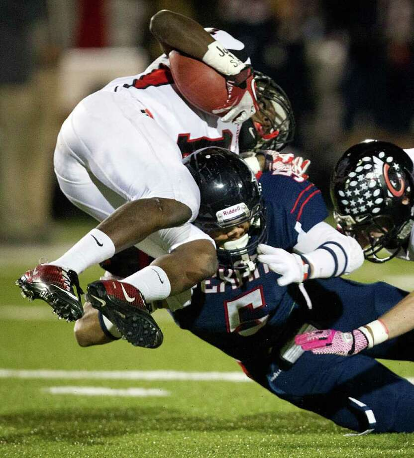 Coldspring running back Sherman Gilbert (1) is upended by Wimberley defensive back Dennis Smith. Photo: Smiley N. Pool, Houston Chronicle / © 2011  Houston Chronicle