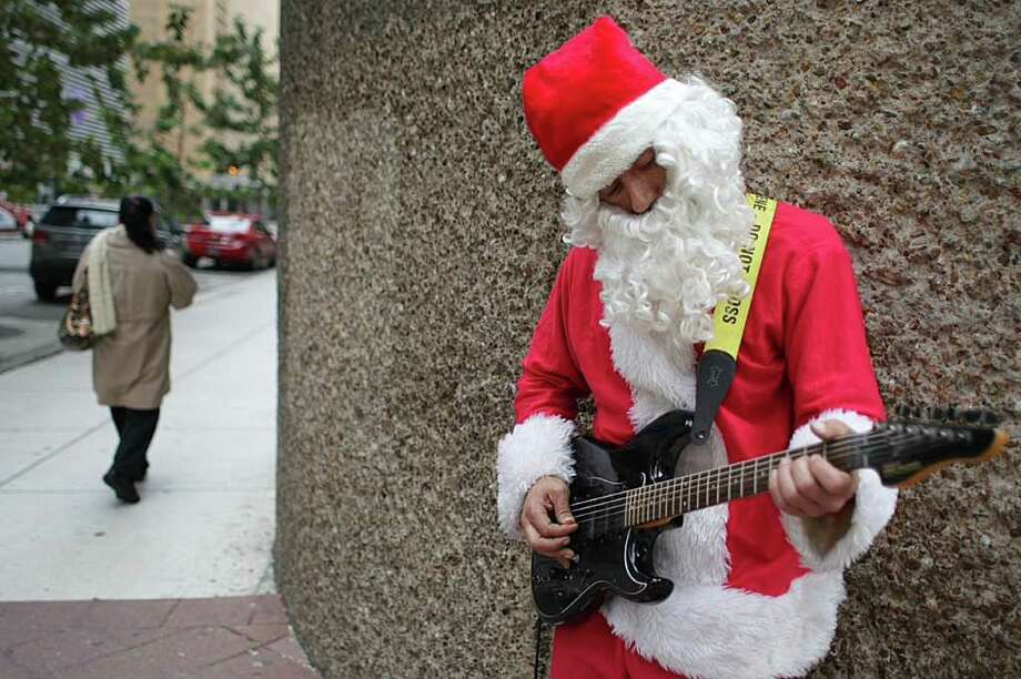 "David Diaz, of Houston, says he plays to cultivate infectious joy while on the corner of Milam and Dallas in downtown Houston. Diaz says, ""if I can make some one smile, maybe they will pay it forward and make someone else smile."" Photo: Nick De La Torre, Houston Chronicle"