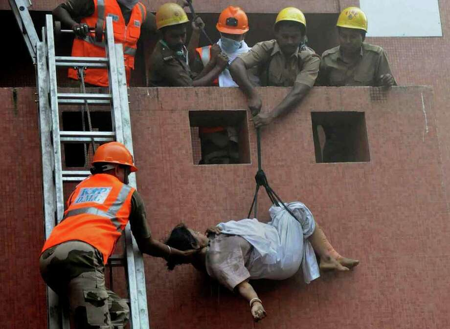 Rescue workers use ropes to evacuate people after a fire engulfed a hospital, in Kolkata, India, Friday, Dec. 9, 2011. Medical staff at an Indian hospital abandoned their patients and fled for safety early Friday as fire and smoke poured through the building, leaving dozens dead, many from smoke inhalation, officials said. (AP Photo) / AP