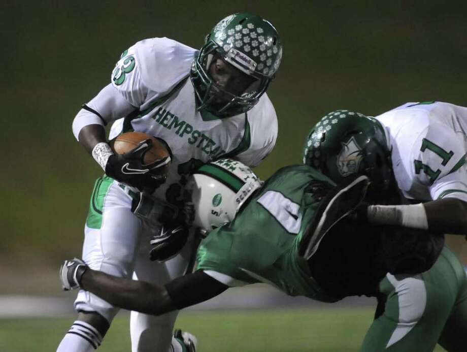 Hempstead senior running back Archie Taylor (23), with help from teammate Trent Momon, tries to break free of Tatum defender Carl Whitaker, Jr. Photo: Jerry Baker, For The Chronicle