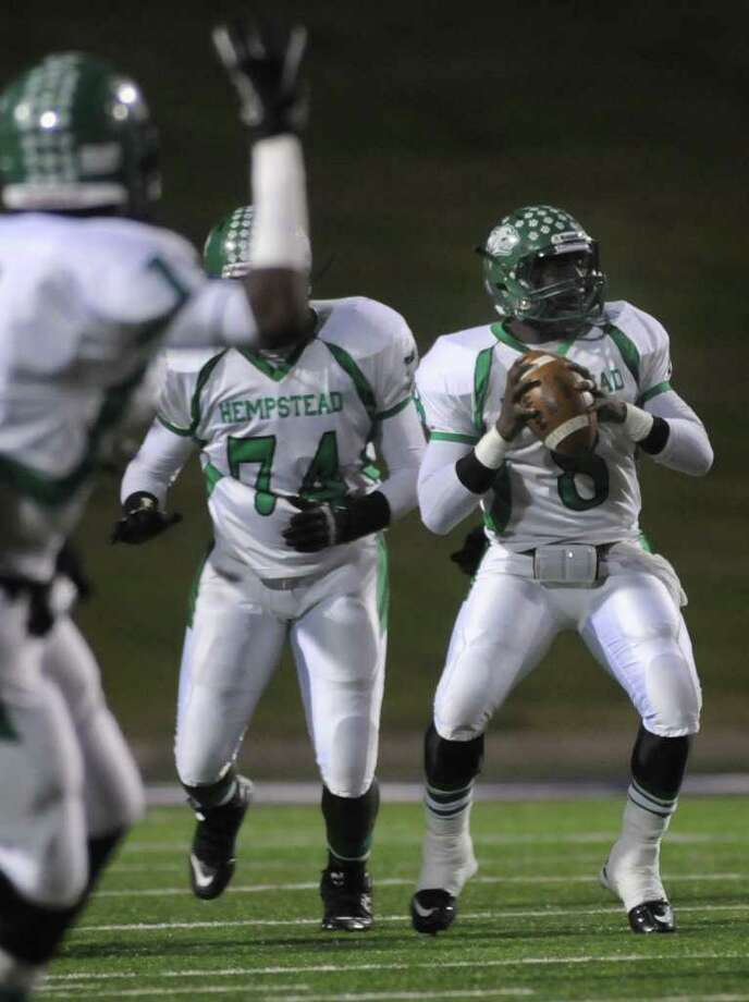 Hempstead senior quarterback Obie Wilder looks for a receiver as teammate Trent Momon, left, waves to his quarterback. Photo: Jerry Baker, For The Chronicle