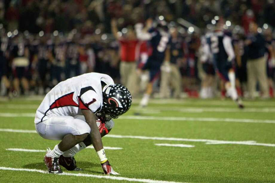 Coldspring running back Sherman Gilbert kneels on the turf as Wimberly players celebrate in the final moments. Photo: Smiley N. Pool, Houston Chronicle / © 2011  Houston Chronicle
